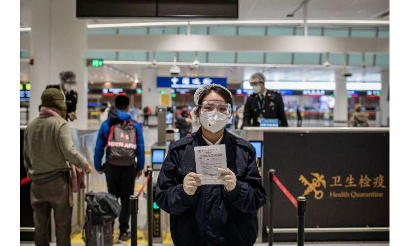 A health quarantine officer (C), wearing protective gear at Daxing International Airport in Beijing, holds a health document to