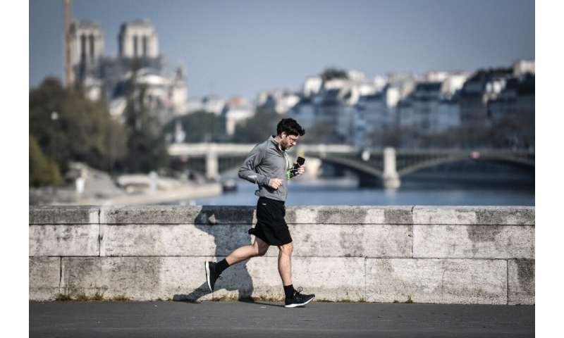 A jogger runs across a bridge in central Paris - joggers will have to keep 10 metres apart once the lockdown ends on May 11