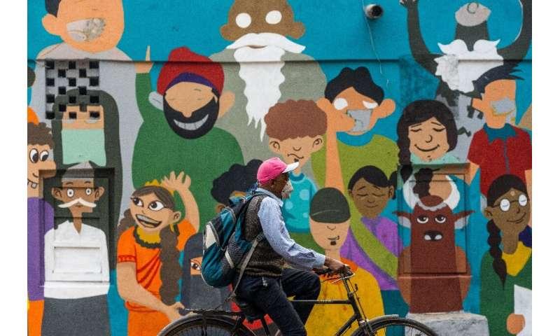 مردی با ماسک ویروس کرونا در کنار خیابانی در دهلی نو سوار می شود