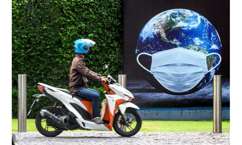 A man rides his scooter in front of a COVID-19 coronavirus related poster  in Bangkok