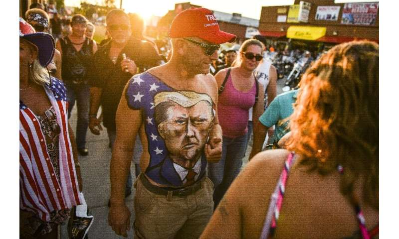 A man walks down Main Street in Sturgis, South Dakota, showing off his chest painted with a portrait of President Donald Trump d