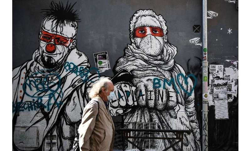 A man walks past a mural in Marseille, southern France