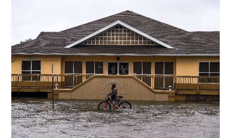 A man walks with his bicycle through a street flooded by rains from Hurricane Sally in downtown Pensacola, Florida