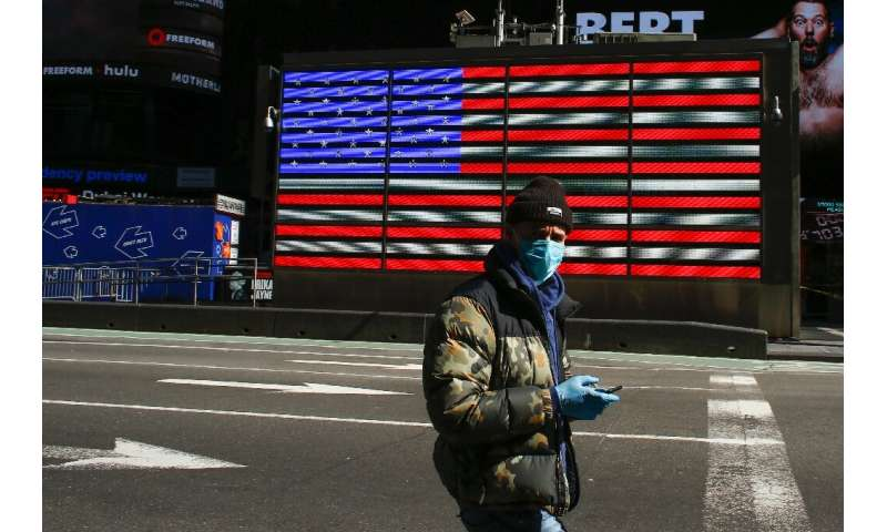 A man wears a face mask as he checks his phone in Times Square on March 22 in New York