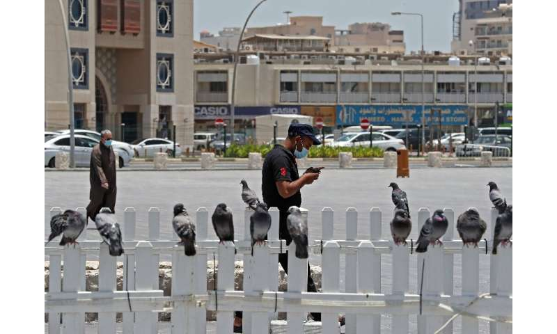 A masked man checks his phone in Qatar where residents and citizens have been required by law to install a coronavirus contact t
