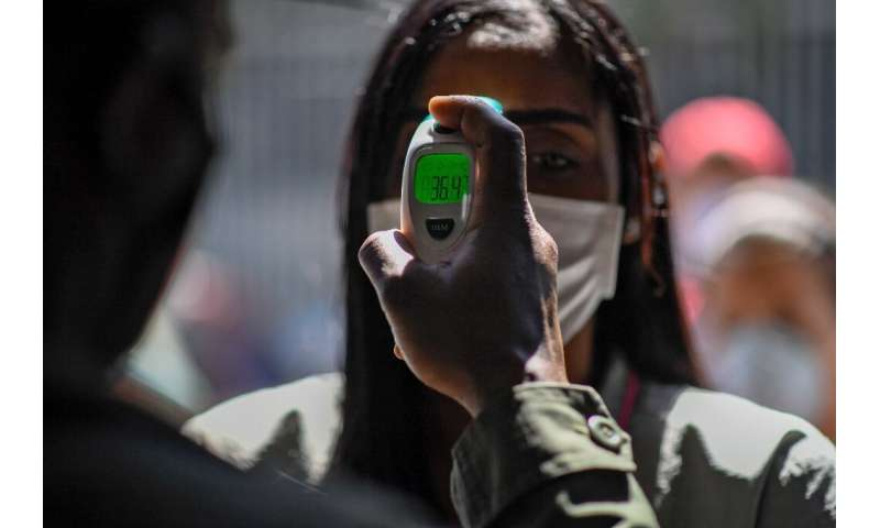 A member of the Bolivarian National Guard checks a woman's temperature outside a market in Caracas, Venezuela on March 20, 2020