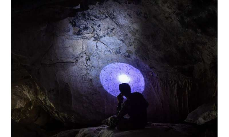 An archaeologist assesses newly discovered cave paintings in Khao Sam Roi Yot National Park in Thailand