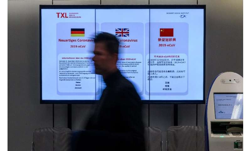 An electronic billboard at Berlin's Tegel airport displays information on the novel coronavirus—Germany and Japan have reported