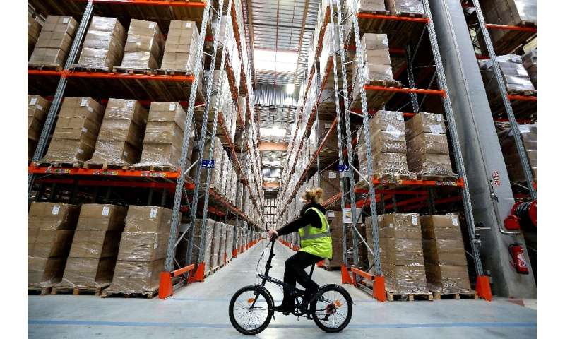 "An employee rides a bicycle through a ""Sante publique France"" warehouse in Marolles, where a billion face masks are be"