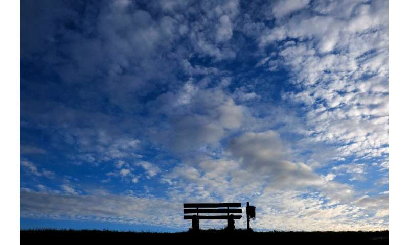 An empty bench silhouettes against the evening sky in Emden, northern Germany, as many activities slowed down or came to a halt