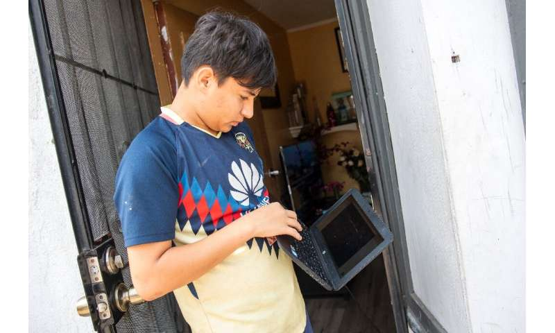 Angel, 13, berdiri di luar rumahnya mencoba menghubungkan komputernya ke hotspot wifi yang disediakan oleh mobil van yang diparkir dari perusahaan JFK