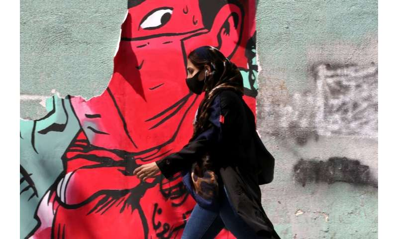 An Iranian woman walks past graffiti in Tehran