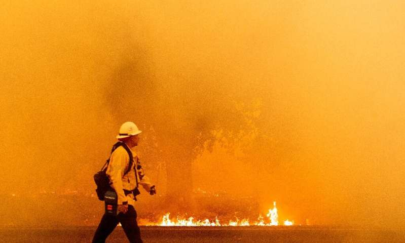 A Pacific Gas and Electric firefighter walks down a road as flames approach in Fairfield, California during the LNU Lightning Co