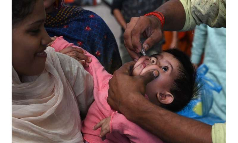 A Pakistani health worker administers polio drops to a child at a railway station during a polio vaccination campaign in Lahore