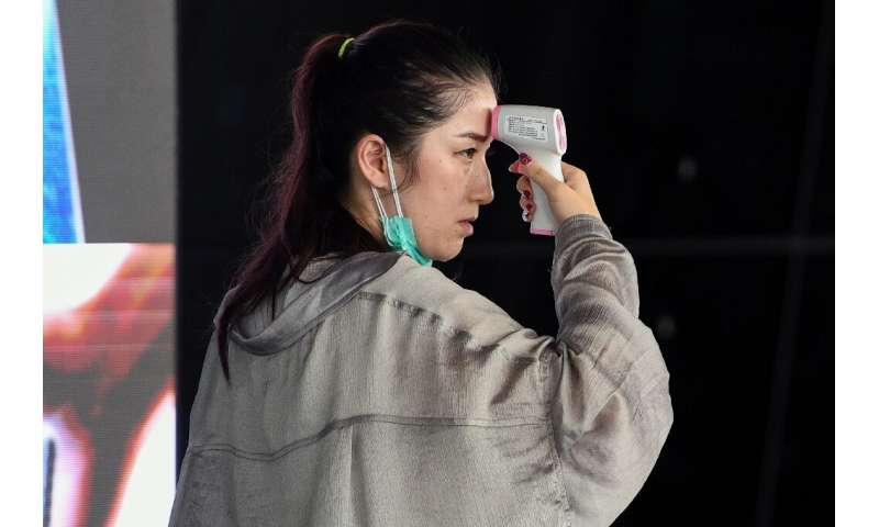 A passenger checks herself with a digital infrared thermometer at Kuala Lumpur International Airport