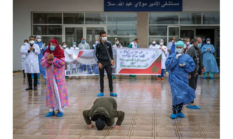 A patient who recovered from Covid-19 kisses the ground and another rejoices with medical staff as they leave a hospital in the