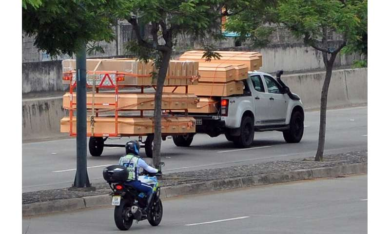 A pick-up truck carries coffins as its drives past the IESS Hospital Los Ceibos in Guayaquil, Ecuador