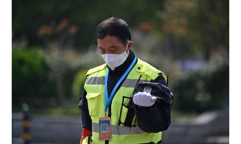 A policeman bows his head in Wuhan as China observed three minutes of silence to mourn those who died in the coronavirus pandemi