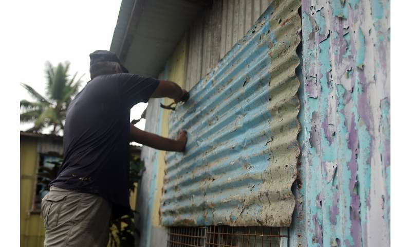 A resident secures his house by placing steel sheets on the windows in Fiji's capital Suva on December 16, 2020, ahead of super