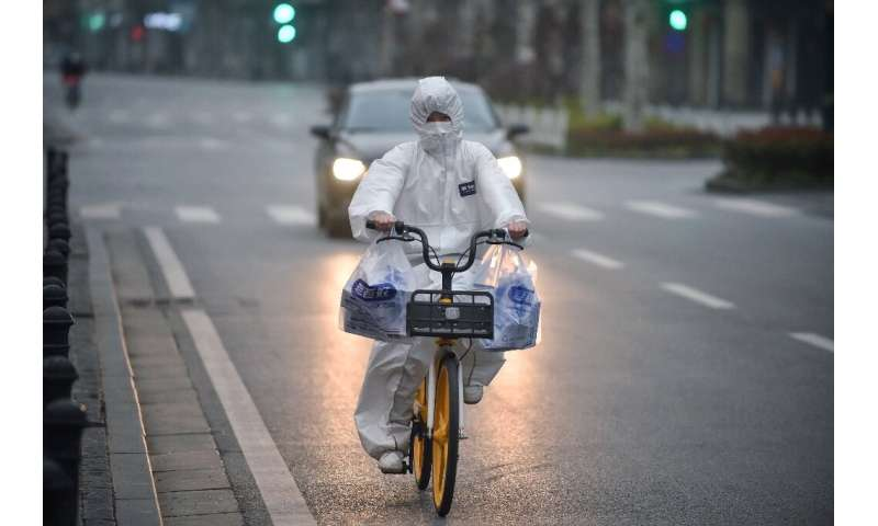 A resident wearing a protective suit rides a bicycle in the virus epicentre of Wuhan in China's central Hubei province