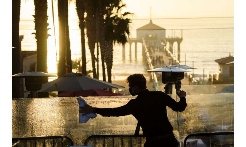 A restaurant employee cleans a plexiglass table divider while preparing for outdoor dining service in Manhattan Beach, Californi