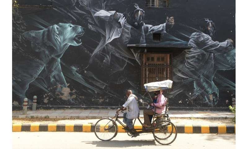 A rickshaw driver carries passengers  past a mural in the Lodhi Art District in New Delhi