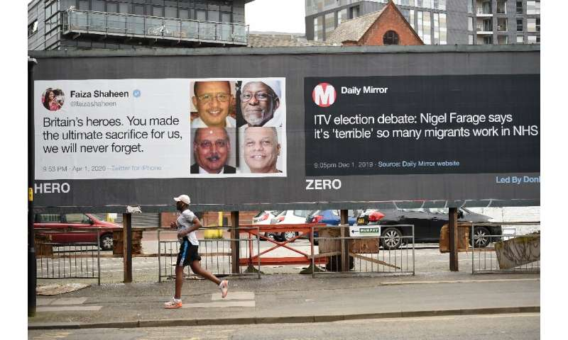A runner passes posters critical of comments made about migrants in Manchester, north-west England