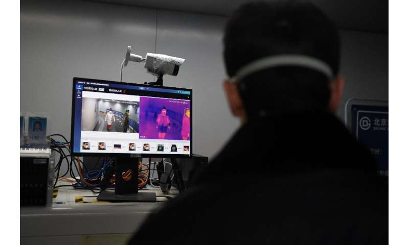A security guard keeps watch as an AI-powered system screens commuters for fevers while they enter a Beijing metro station