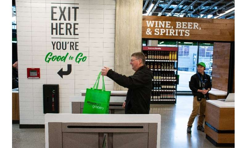 A shopper exits Amazon Go Grocery on February 26, 2020 in Seattle, Washington, the first full-sized retail grocery location that