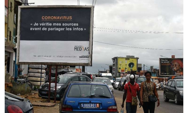 A sign in Abidjan reads 'Coronavirus - I check my sources before sharing news' to warn people against fake news and misinformati