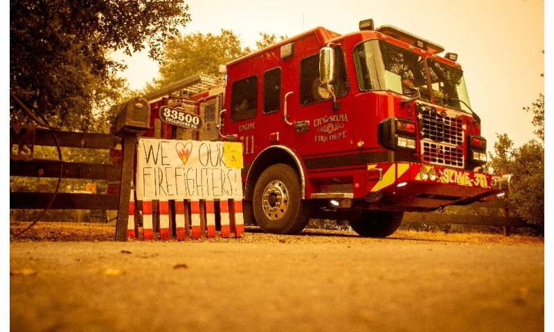 A sign is posted next to a fire vehicle as flames continue to consume the area during the Creek fire in Fresno County, Californi
