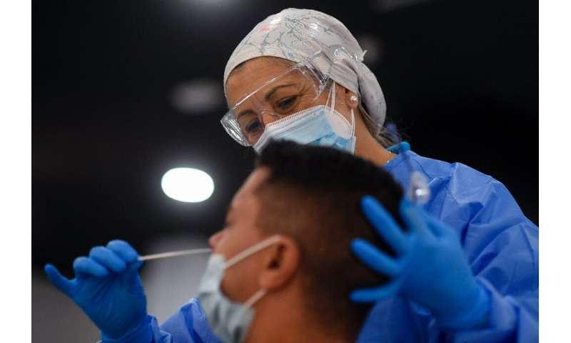 A Spanish medical worker takes a swab sample from a man in Madrid, Spain