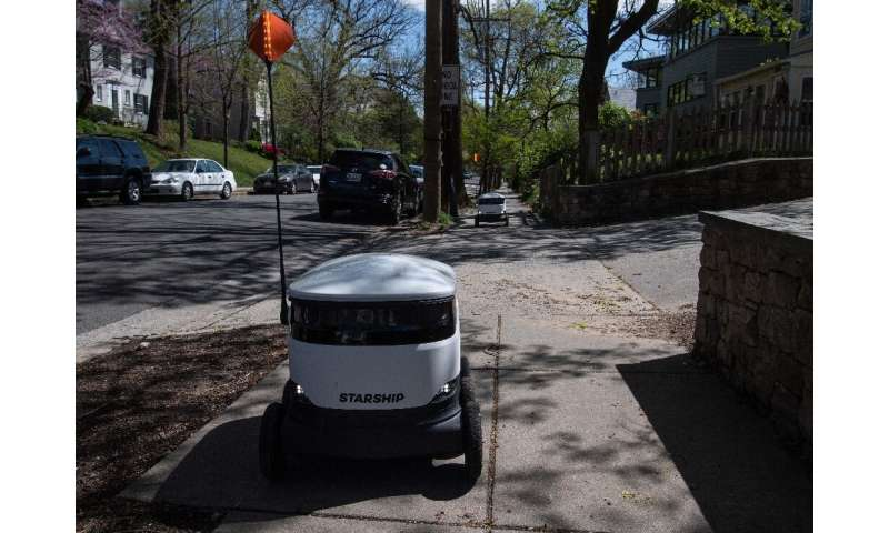 A Starship delivery robot leaves the Broad Branch Market grocery store in Washington, DC, on its way to a home customer