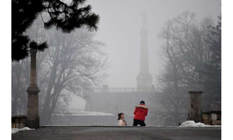 "A tourist poses for a picture near ""The Victor"" (Pobednik) monument in Belgrade"