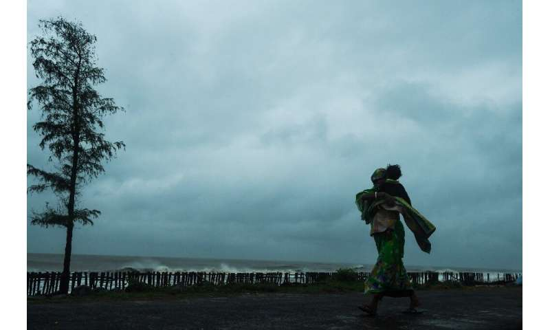 A woman carries her child as she walks along a road near the Tajpur Beach to take shelter ahead of the expected landfall of Cycl