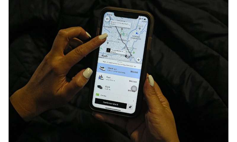 A woman checks the Uber transport application on her mobile phone after authorities ordered its suspension in Colombia, in Bogot