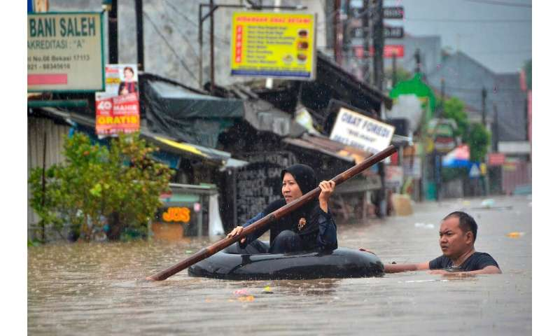 A woman crosses a flooded area in an inflated inner-tube in Bekasi, near Jakarta