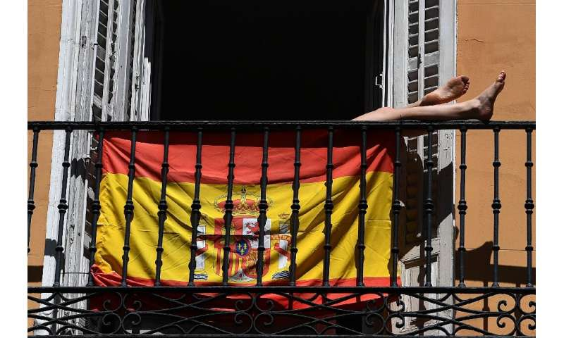 A woman sunbathes behind a Spanish flag on her balcony in Madrid during the national lockdown