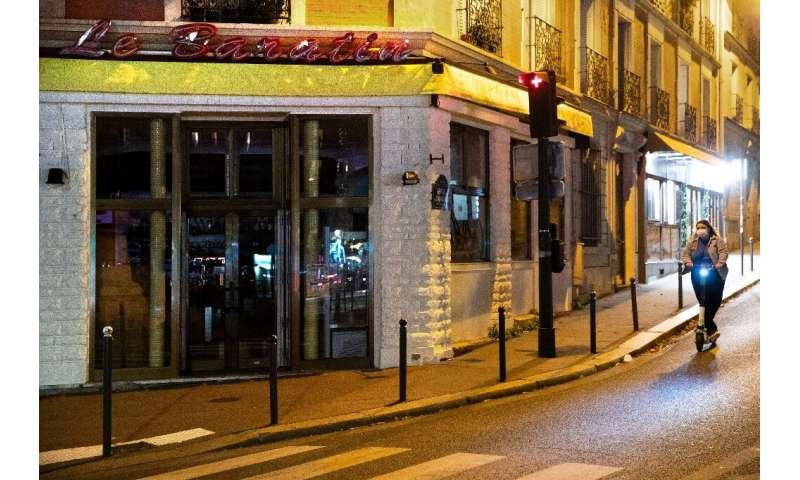 یک زن در حین قفل دوم در کنار یک رستوران بسته در فرانسه قدم می زند