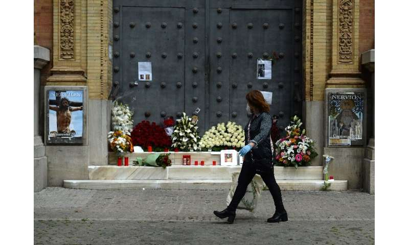 A woman walks past a church in Seville, adorned with flowers and candles left by the faithful after Easter processions were canc