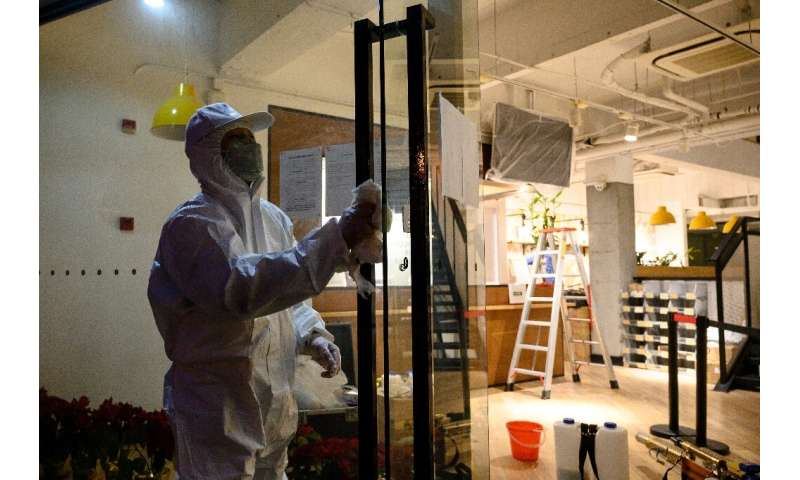 A worker wearing a protective suit disinfects door handles of a business establishment in Shanghai