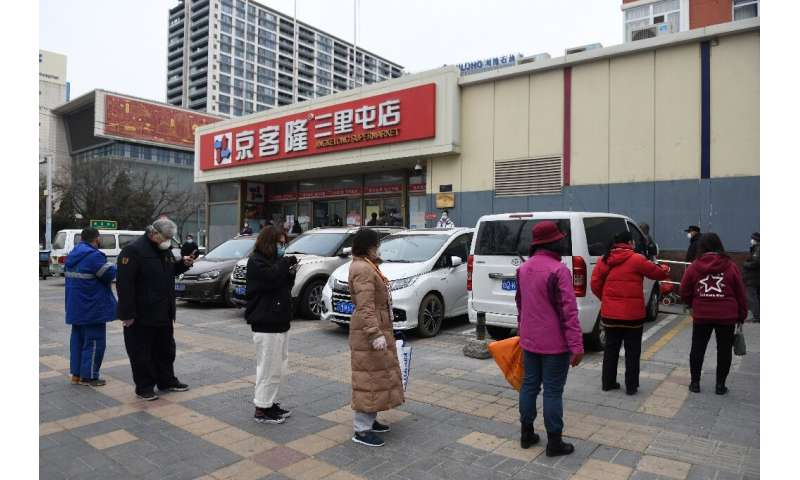 Beijing supermarkets now have restrictions on the number of shoppers inside, meaning some have to wait outside
