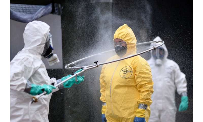 Brazil's military, firefighters and Civil Defense members disinfect each other after cleaning a bus station in Belo Horizonte, B