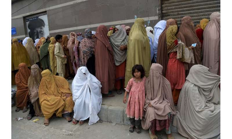 Burqa-clad women in Peshawar wait to collect cash under the governmental Ehsaas Emergency Cash Programme for families in need du
