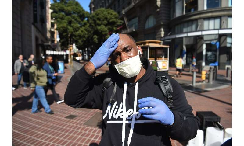 Cameron Nightingale, trying to protect himself from the new coronavirus, adjusts his mask and gloves in San Francisco, after off