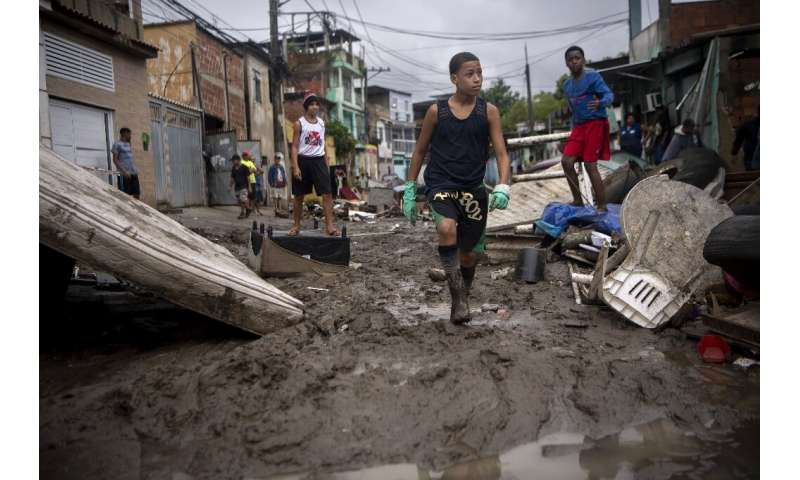 Children walk in the mud following heavy rains during the weekend, in Realengo neighborhood, in the suburbs of Rio de Janeiro, B