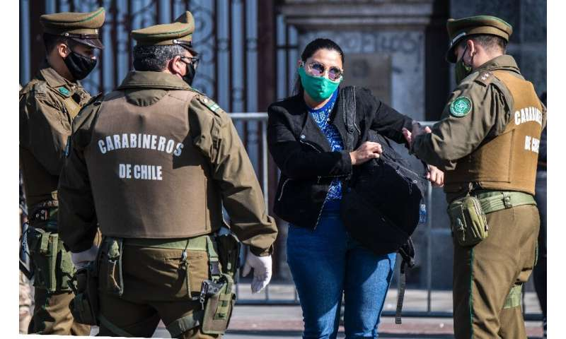 Chilean security forces check a woman's documents as they enforce a total quarantine to prevent the spread of the coronavirus in
