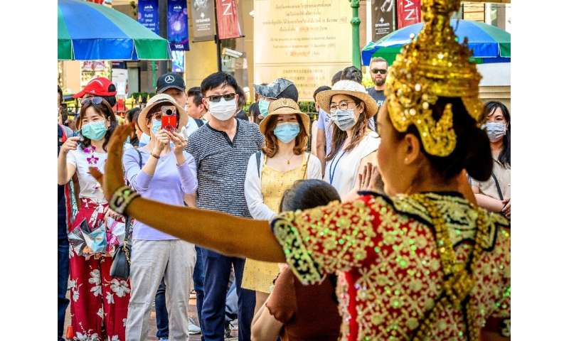 Chinese tourists wearing face masks watch a traditional Thai dance at Erawan shrine, a popular landmark in Bangkok