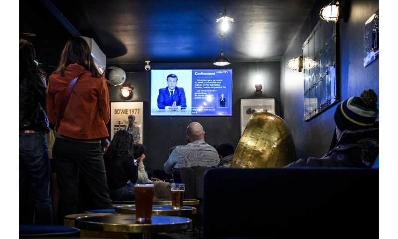 Clients watch Macron's evening televised address to the nation in a cafe in Bordeaux, which will have to close on Friday.