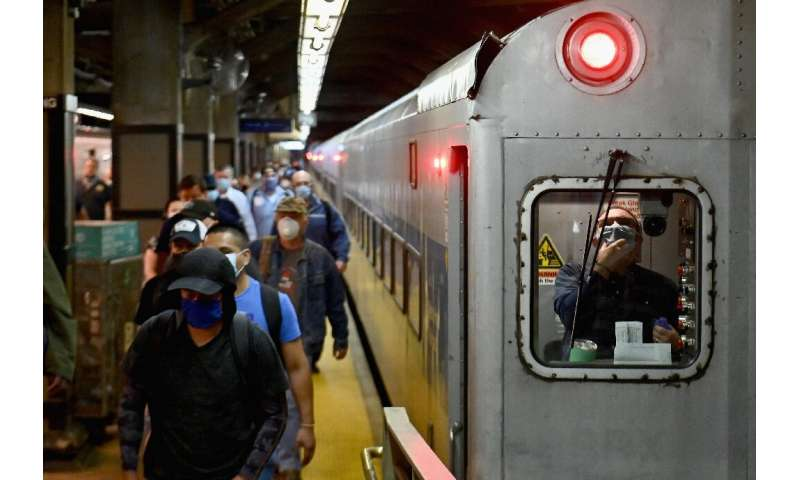 Commuters arrive at New York's Grand Central Station during morning rush hour as the city entered phase one of its coronavirus r